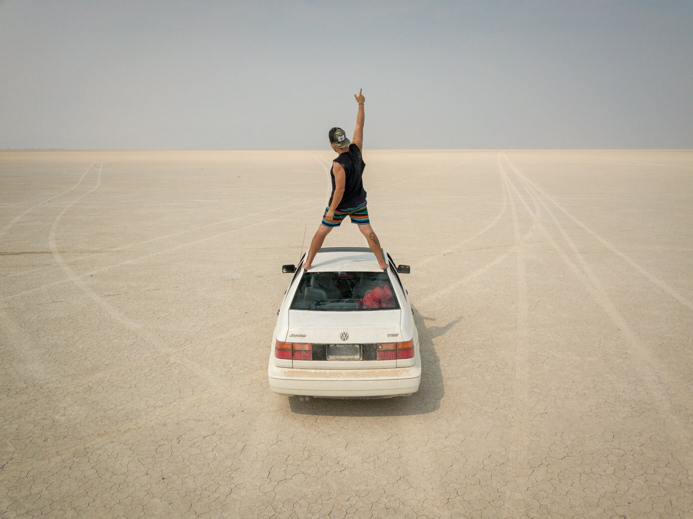 Man standing on car in Alvord Desert