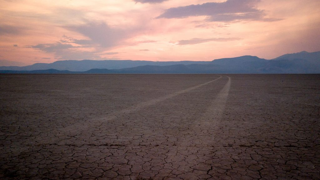 Tire tracks leading to a sunset in Alvord Desert