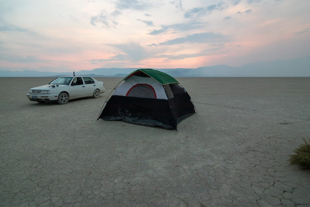 The tent and car on the Alvord Desert after sunset.