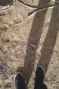 Eli's feet and shadow above the desert dirt.