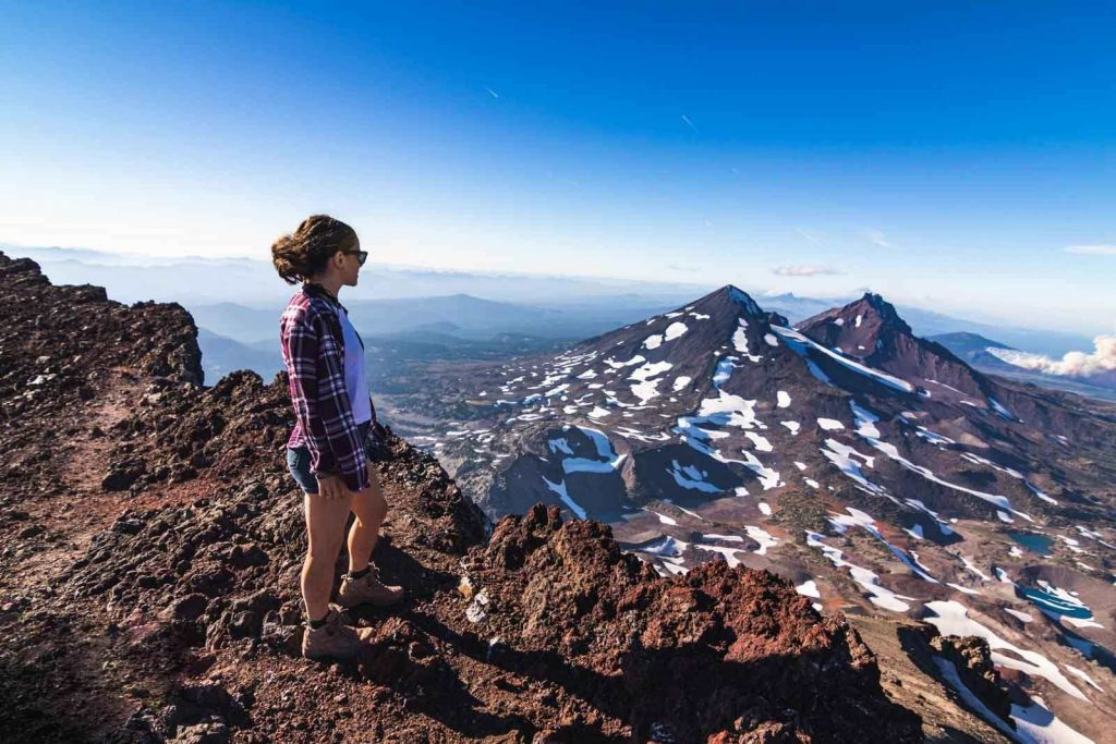 Nina looks out over snowy mountains from South Sisters hikes