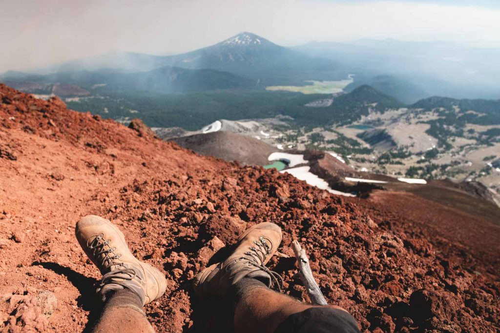 Hiker's legs on mountain top with mountain and glacier views in front while hiking south sister