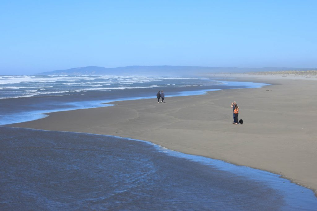 View of people walking on Bullards Beach near one of the best Oregon Lighthouses