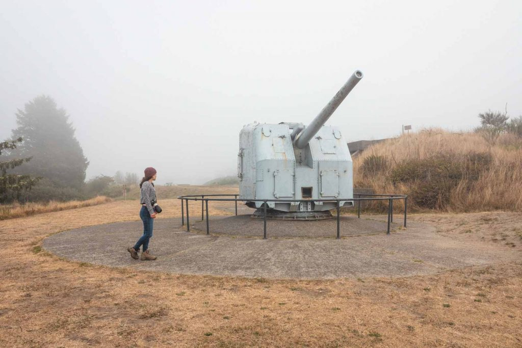 Person in front of military gun at Fort Stevens Oregon Coast State Park
