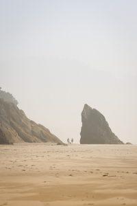 Foggy beach and large rocks at Hug Point Oregon Coast State Park