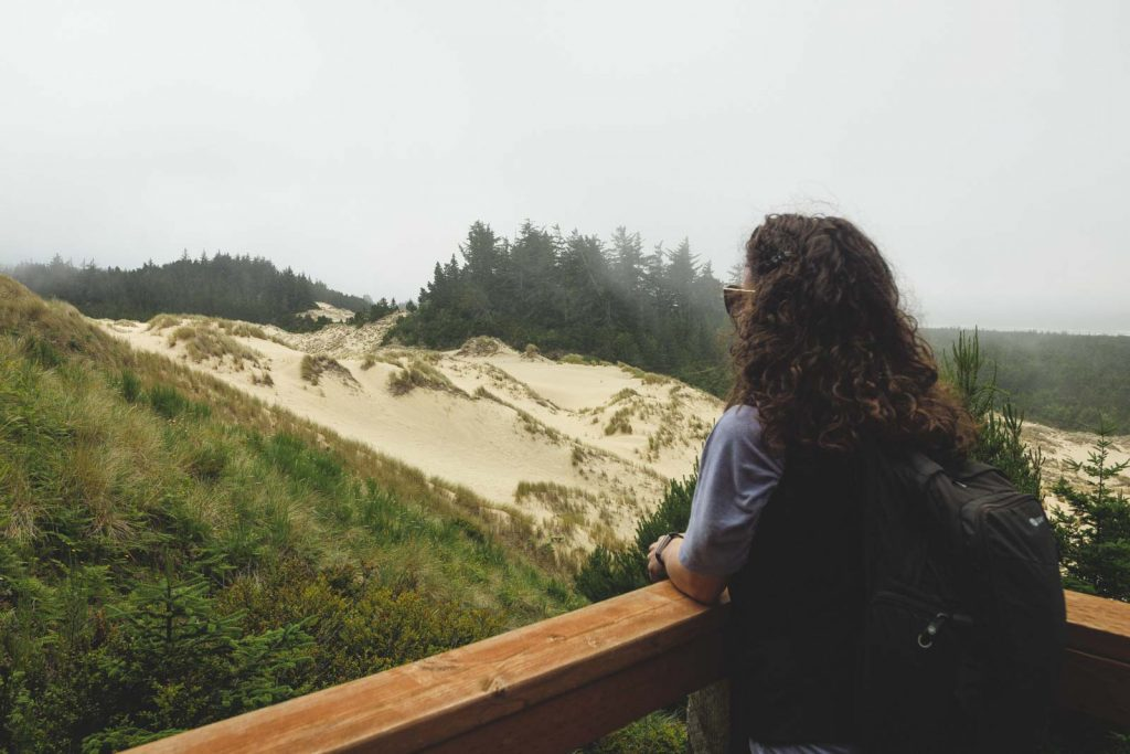 Nina looking out over sand dunes at Oregon Dunes National Recreational Area on the Oregon Coast