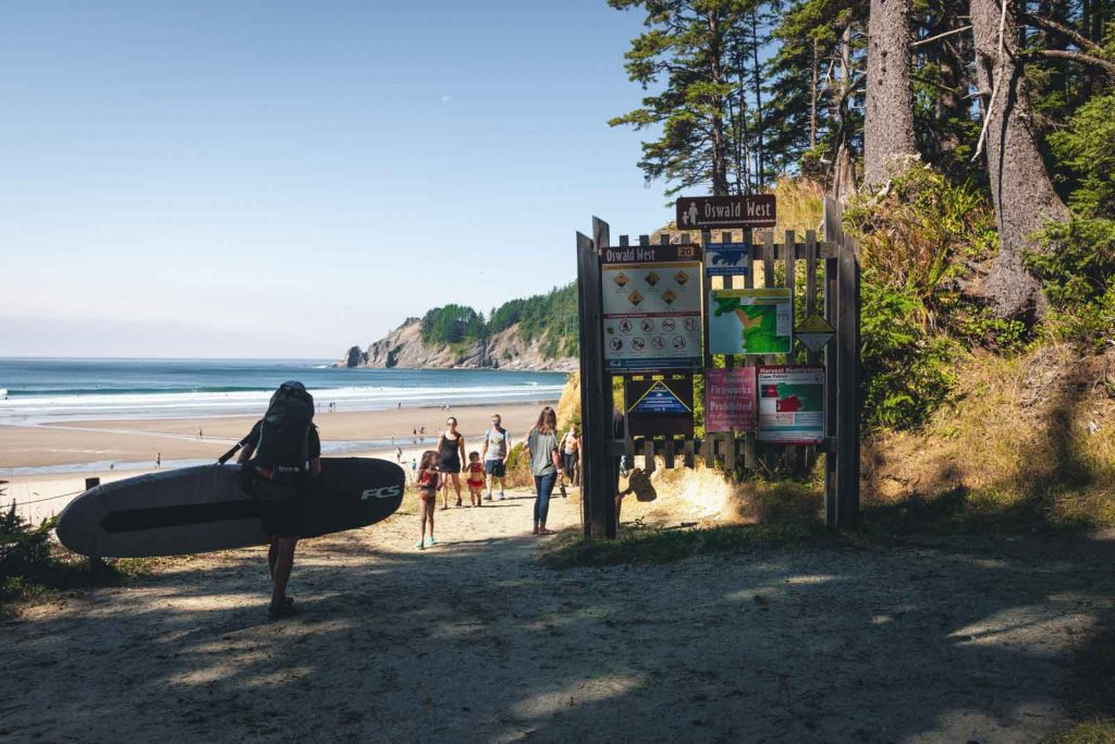 Person with surfboard by large sign with beach in the background at Oswald West, one of the Oregon Coast State Parks