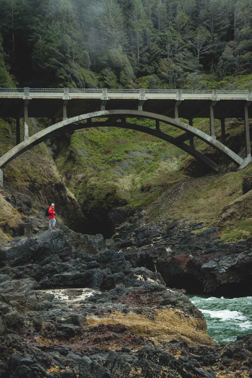 Thor's Well Bridge with person standing on rock in foreground. Near Heceta Head Lighthouse, one of the top Oregon Lighthouses
