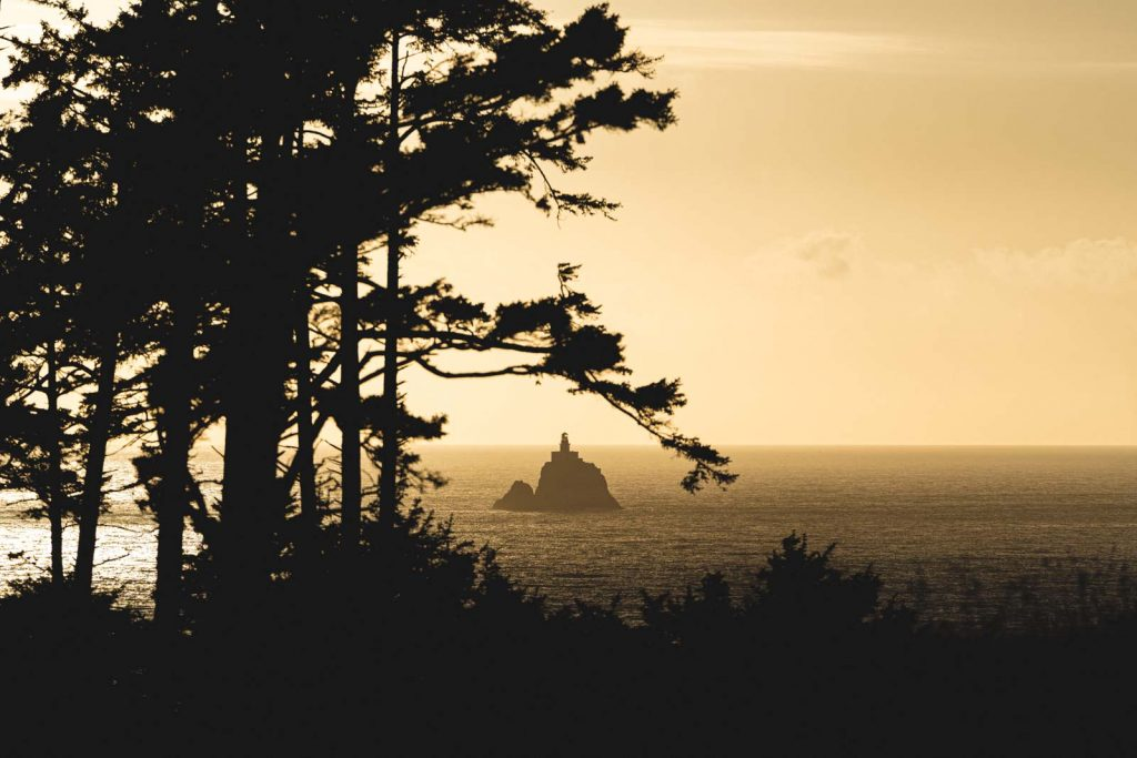 View through trees to Tillamook Rock Lighthouse surrounded by ocean, one of the most scenic Oregon Lighthouses