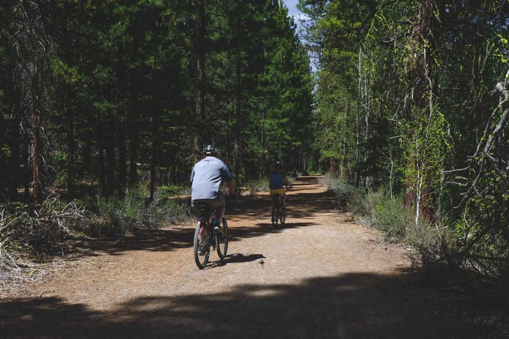 Mountain bikers on a dirt trail in the forest at Newberry National Volcanic Monument