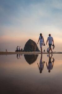 Two people walking in beach by Haystack Rock near Hug Point