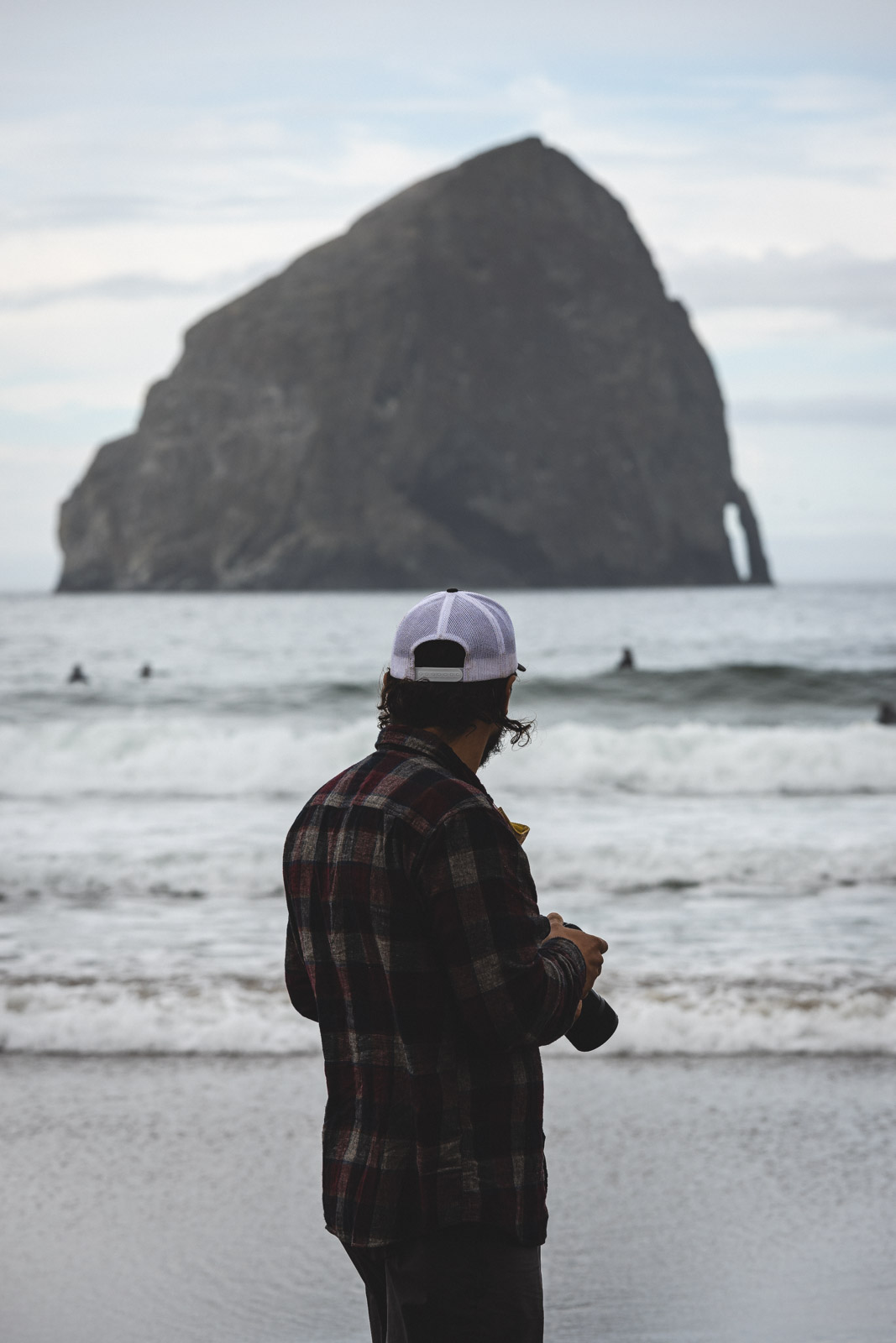 Man standing with camera and looking out to rock island in ocean at Cape Kiwanda, one of the Oregon Coast beaches