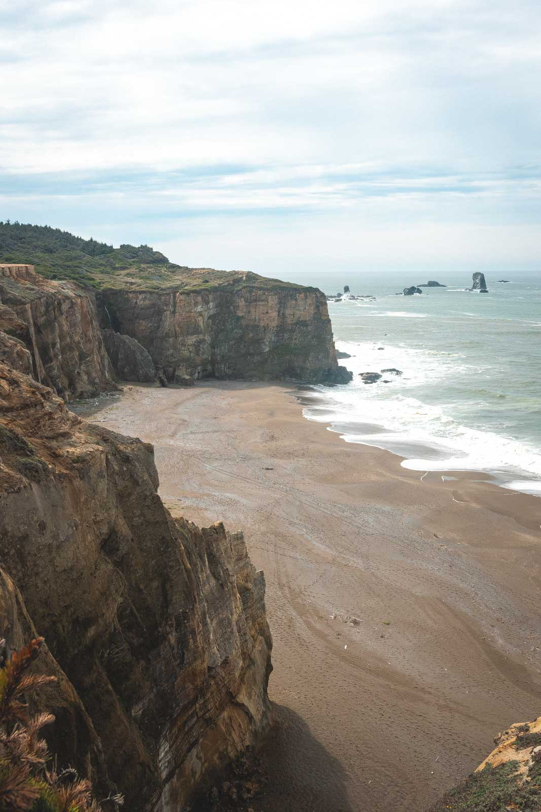 View over beach and seacliffs at Floras Lake State Park, one of the best beaches on the Oregon Coast