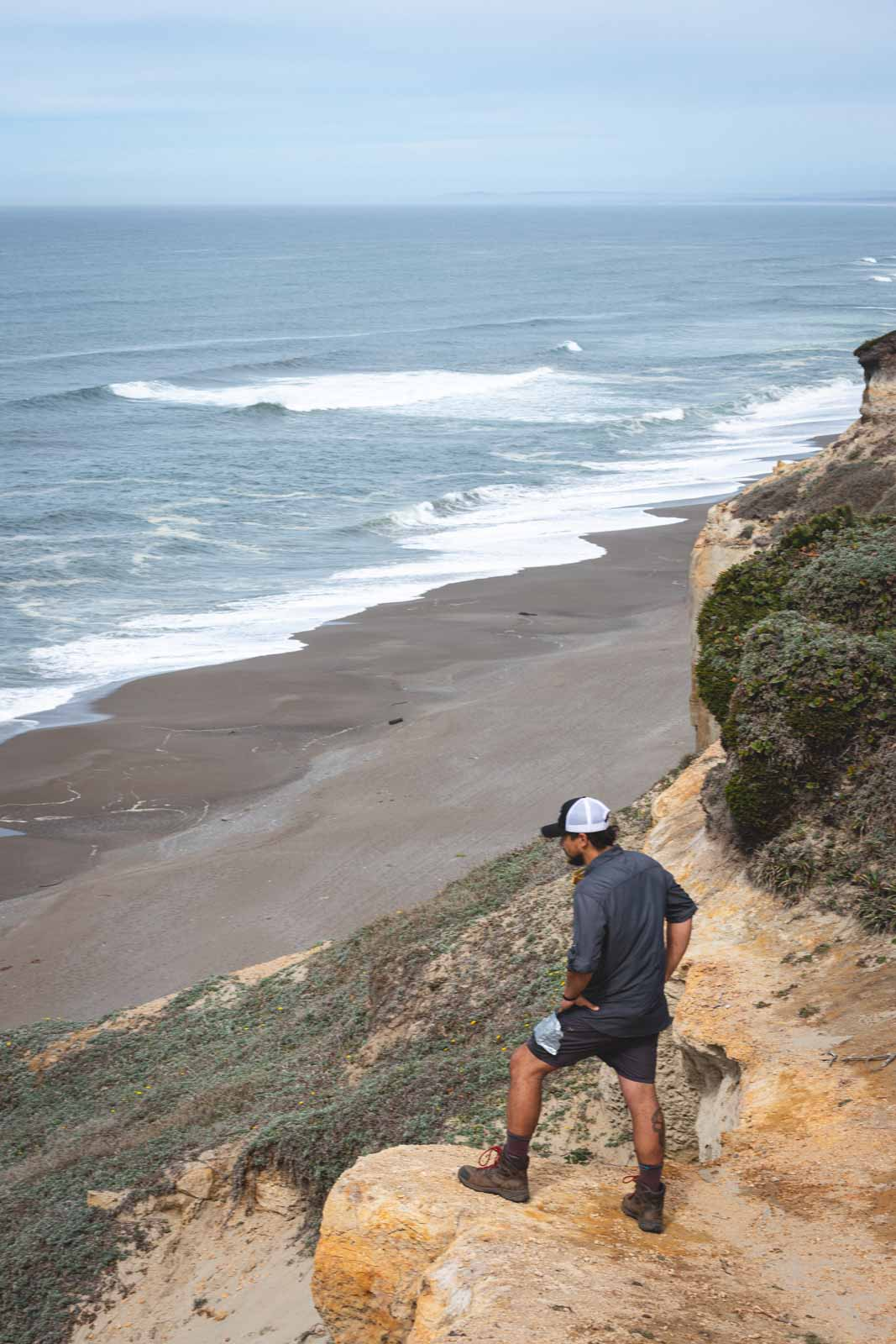 Man hiking and looking out over beach and ocean at Floras Lake State Park, home to one of the best beaches in Oregon