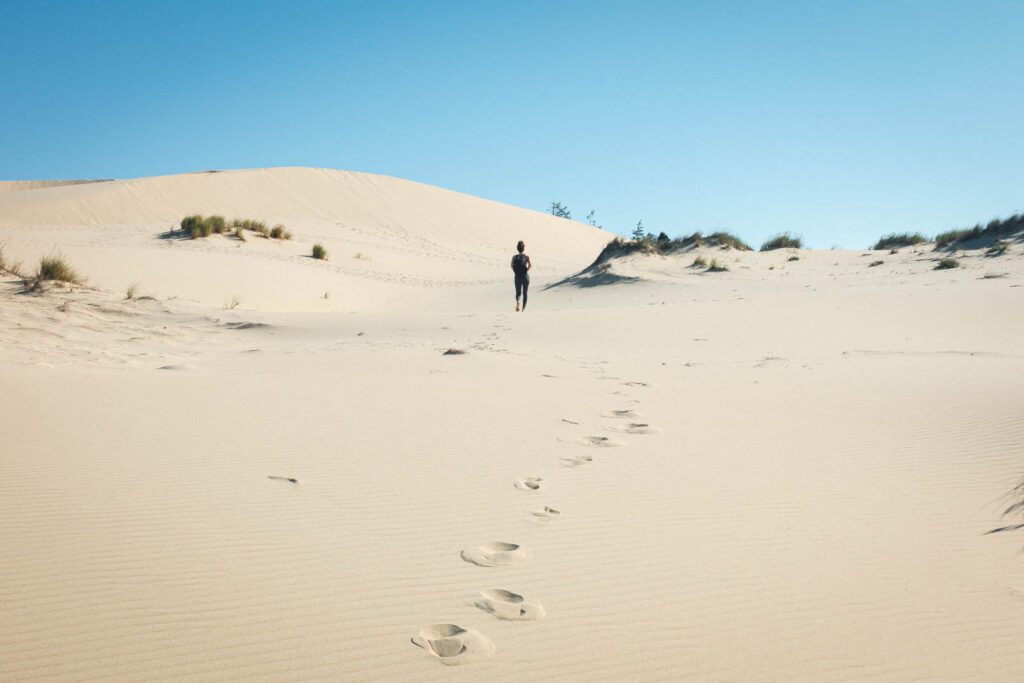 Person hiking in sand dunes to John Dellenback trails beach, one of the best beaches in Oregon