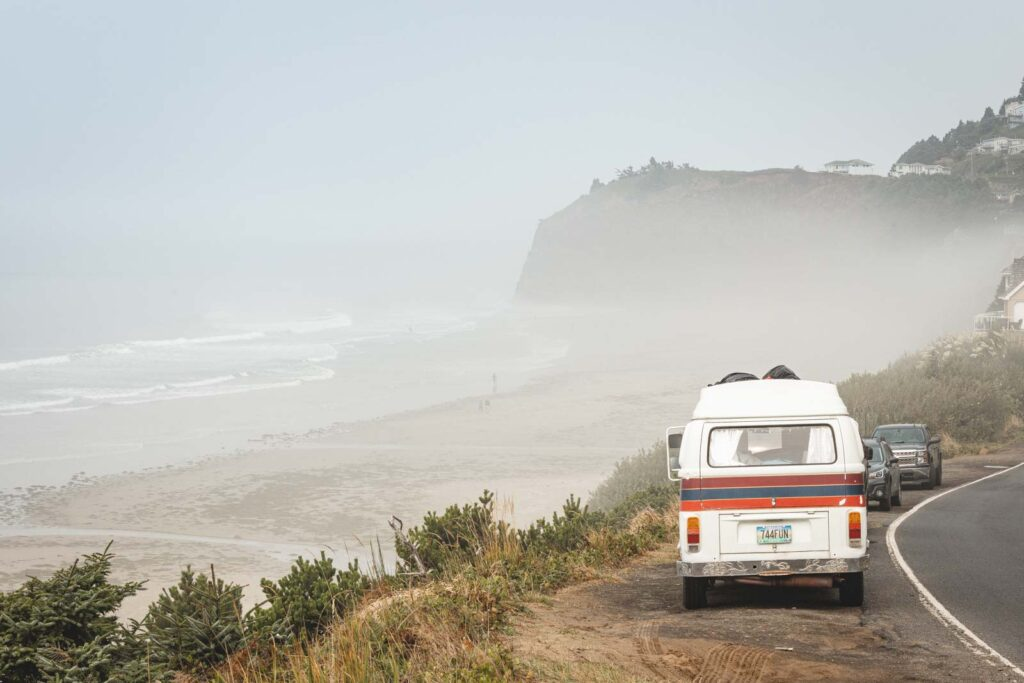 VW van on cliffside with foggy beach and seacliffs in distance at Oceanside Beach in Oregon