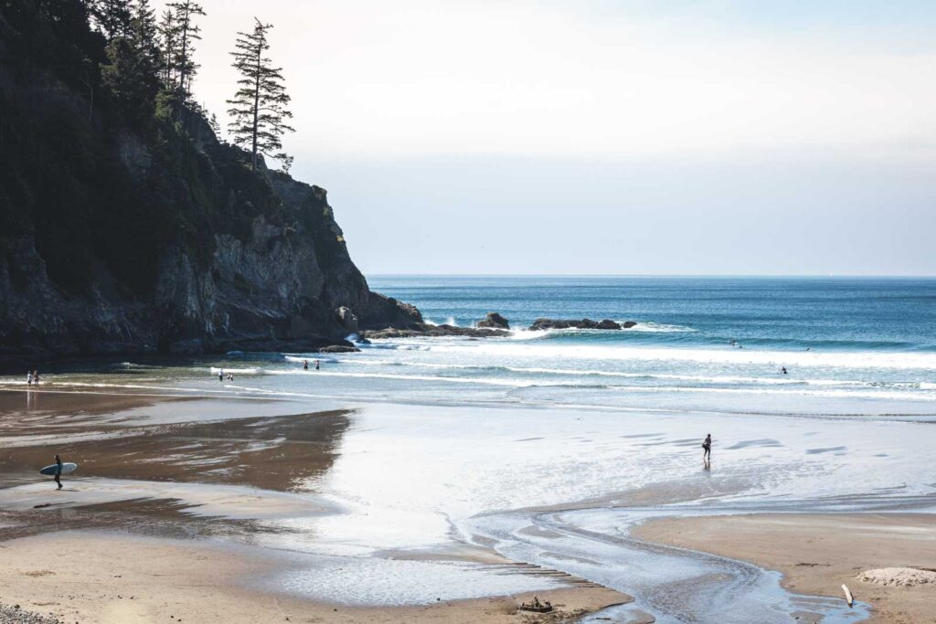 Beach at low tide with person walking on beach and rock outcrop to left of frame at Short Sands Beach in Oregon