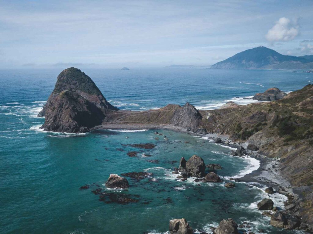 Aerial view over rocky islands and peninsula and ocean at Sisters Rock State Park, home to one of the best beaches in Oregon