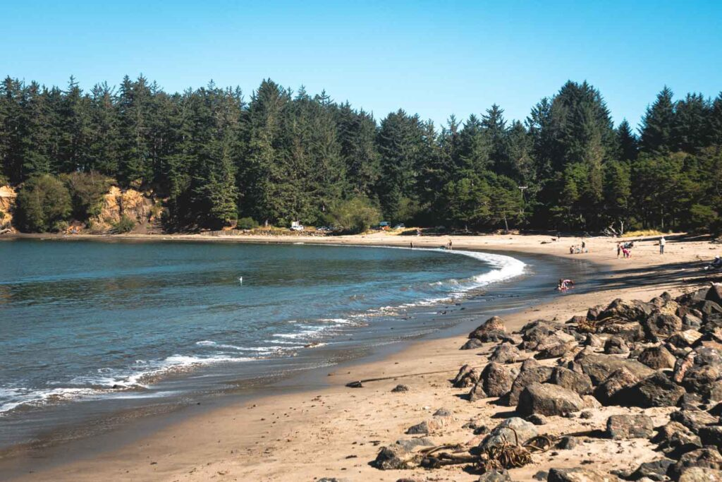 Sandy cove beach with forest in background at Sunset Bay State Park, home to one of the best beaches in Oregon