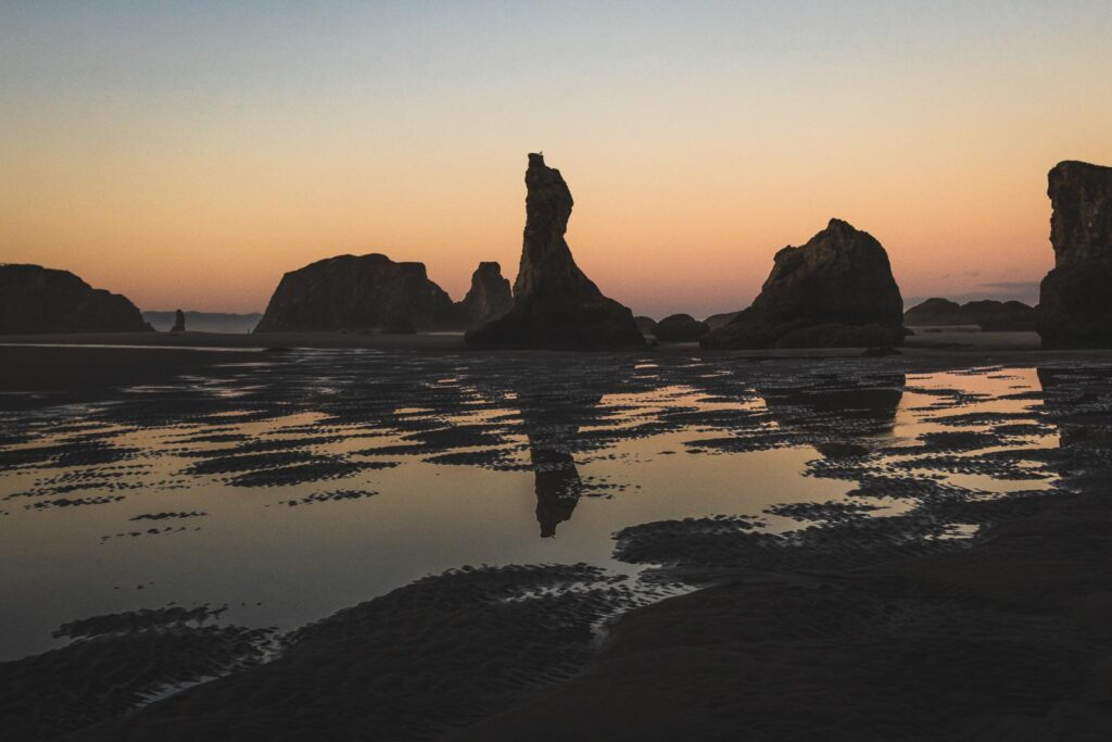 Rock formations with water in foreground at sunset at Bandon Beach in Oregon