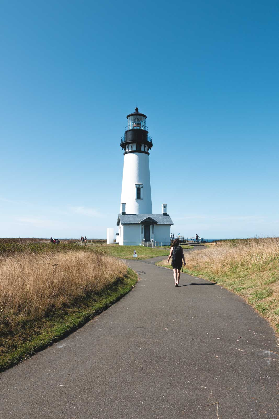 Yaquina Head Lighthouse with person walking path towards it