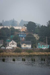 Bayfront houses in the fog with water in foreground