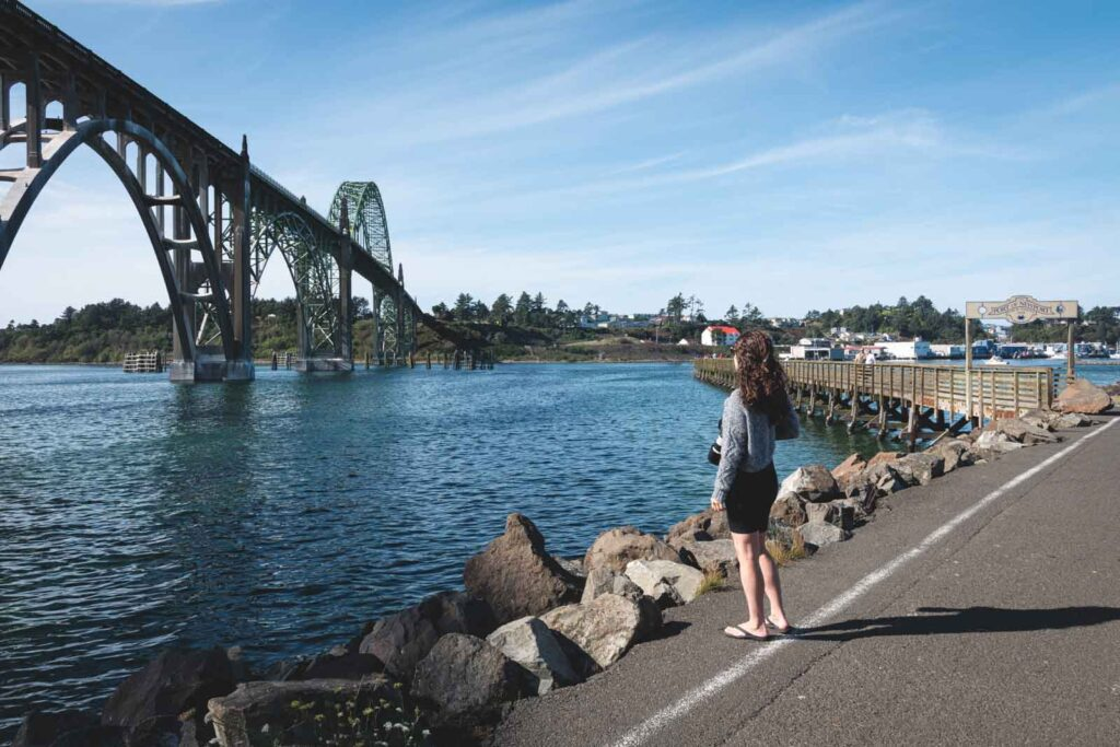Woman standing on path and looking over to bridge in Newport, Oregon