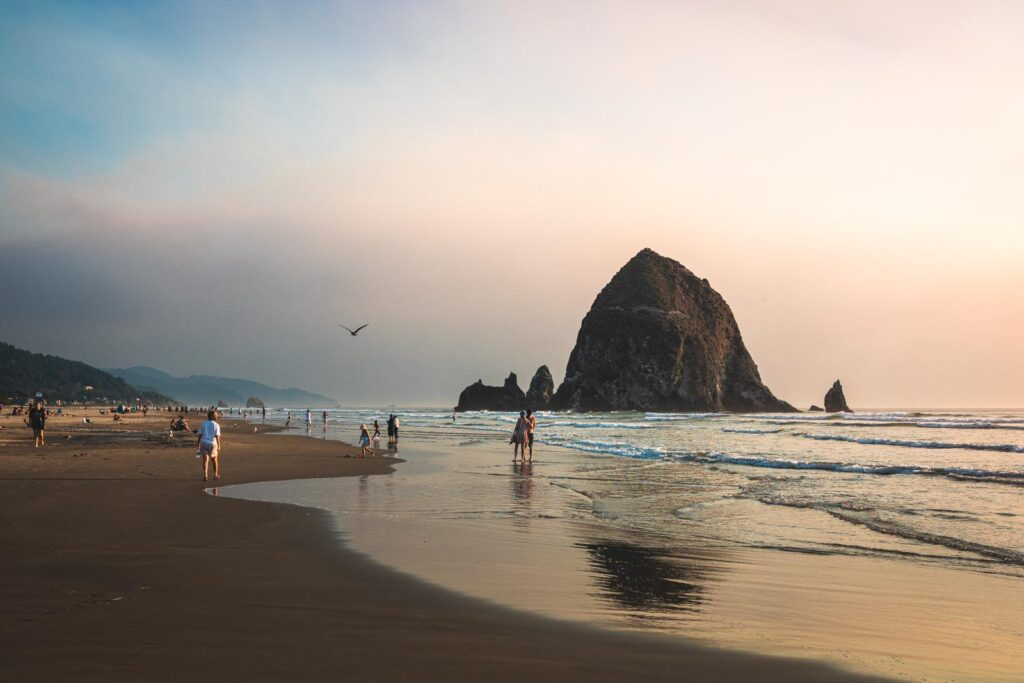 People walking on Cannon Beach with Haystack Rock, one of the best things to do in Seaside Oregon