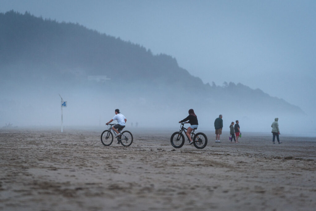 Bikers on fat bikes on a foggy beach - one of the things to do in Newport Oregon