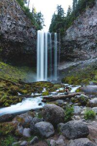 Hiker looking up at Tamanawas Falls in Oregon