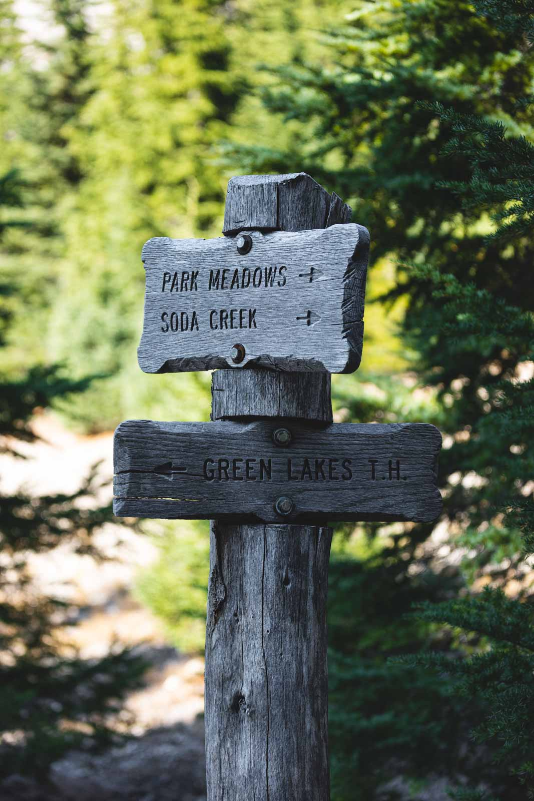 Wooden hiking directions sign on the Green Lakes trail