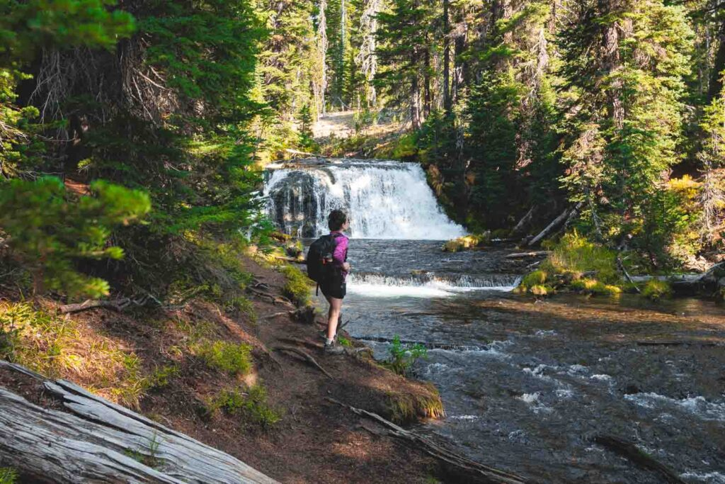 Woman standing in front of waterfall on the Green Lakes trail