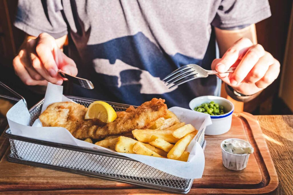Person eating fish and chips - sampling the food scene is one of the best things to do in Seaside