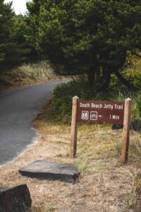Sign beside road for South Beach State Park trail near Newport, Oregon