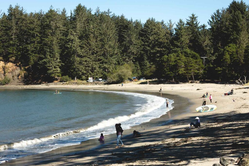 Curving beach with forest in background at Sunset Bay State Park in Oregon