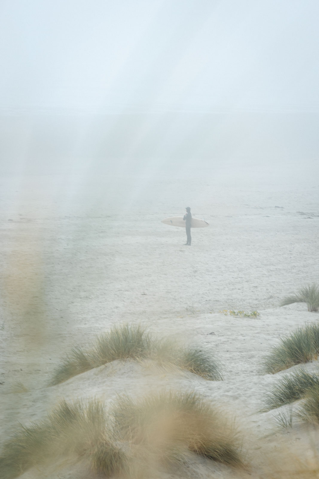 Surfer on the beach in the fog at South Beach State Park near Newport in Oregon