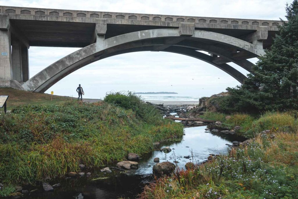 Person standing under bridge with ocean in background at Beverly Beach near Newport Oregon