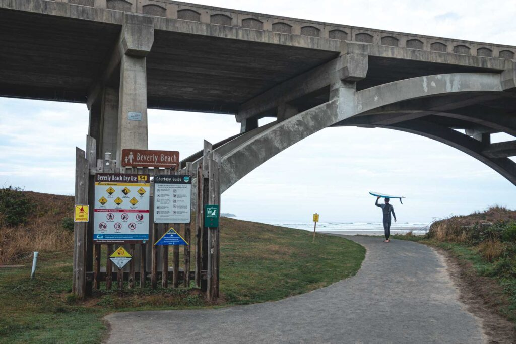 Surfer with surfboard walking to beach under bridge at Beverly Beach State Park