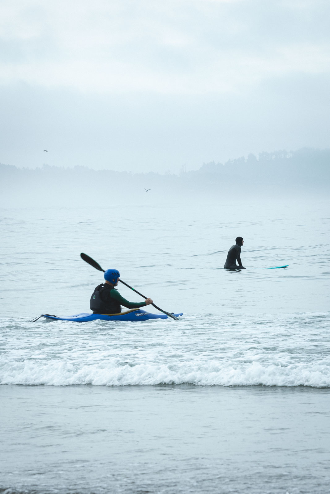 Kayaker and swimmer in water at Otter Rock State Park in Oregon