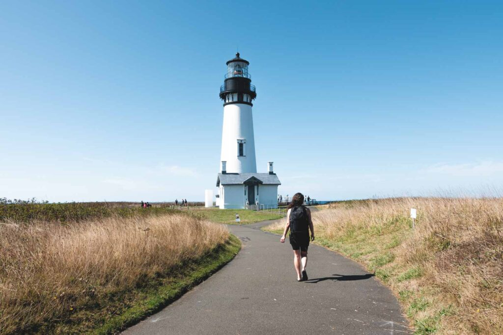 Woman walking path to Yaquina Head Lighthouse in Newport, Oregon