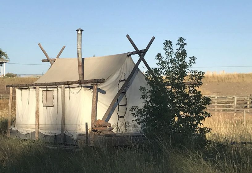 Wall tent with chimney beside a bush - a glamping in Oregon option