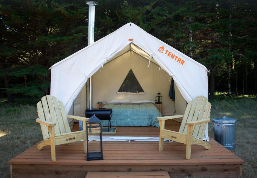 Glamping tent with chairs on deck in front at Cranberry Farms