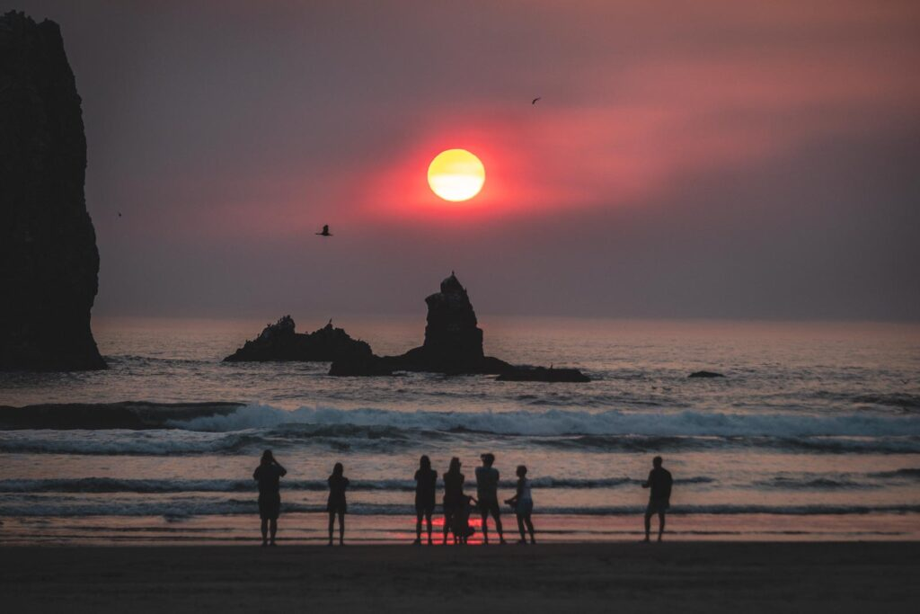 People on beach watching sunset on Cannon Beach out to ocean and rocky island