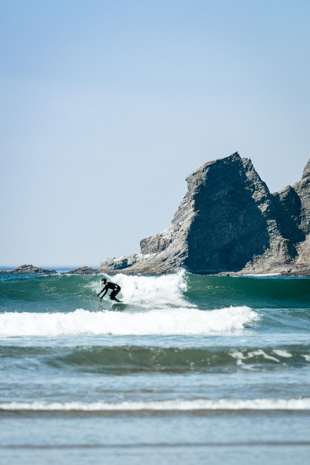 Surfer surfing a wave with rocky outcrop in background at Short Sand Beach near Cannon Beach
