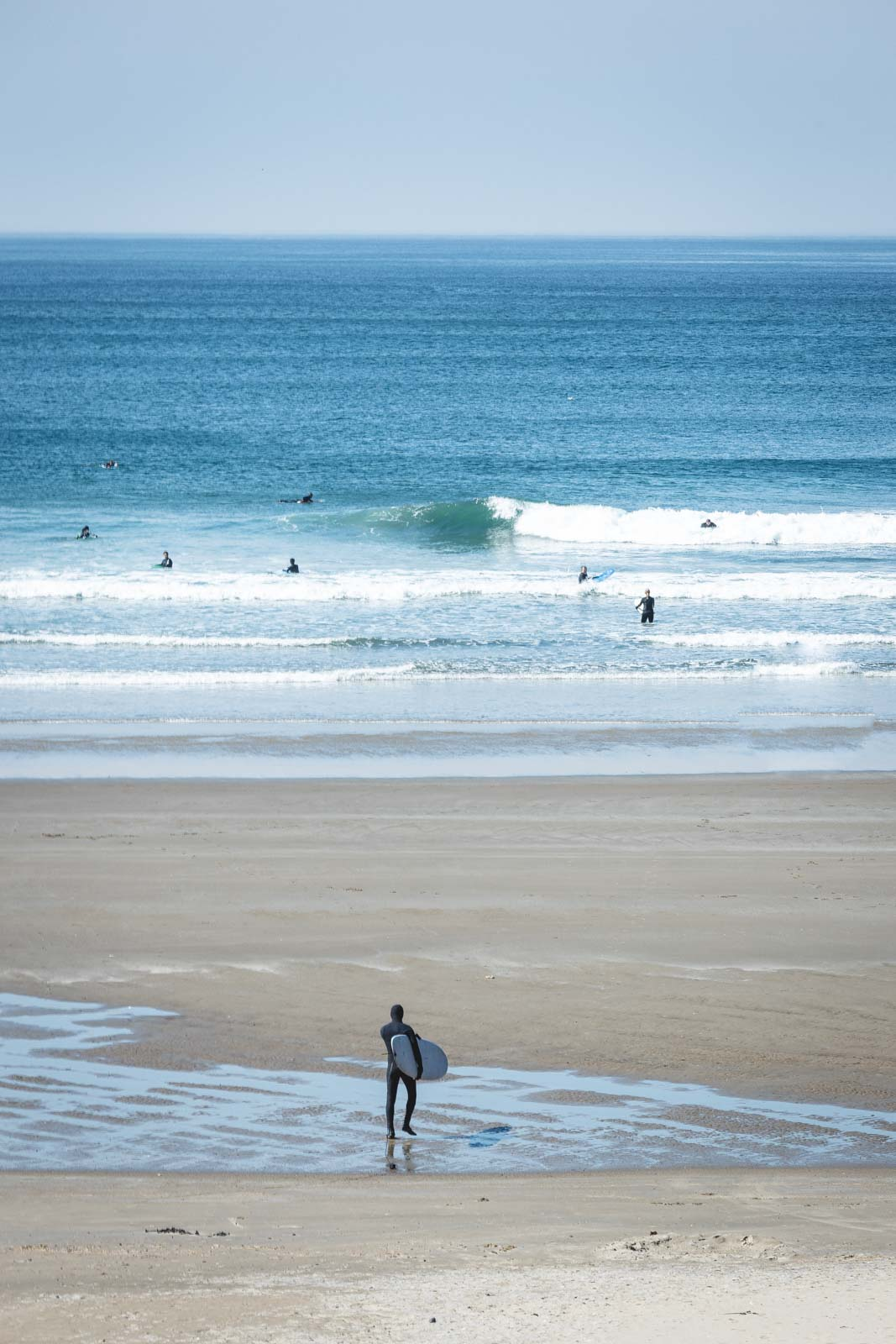 Surfer walking across sand to ocean at Short Sand Beach - one of the best things to do near Cannon Beach
