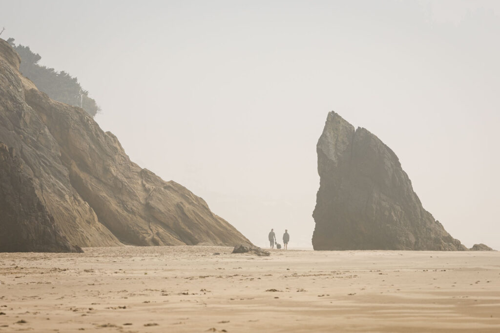 Misty view of people walking on a beach in the distance surrounded by large rocks at Hug Point