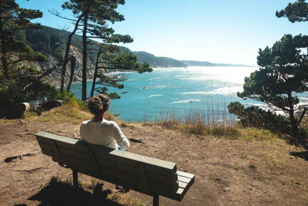Woman sitting on bench and looking out to sea at Cape Arago