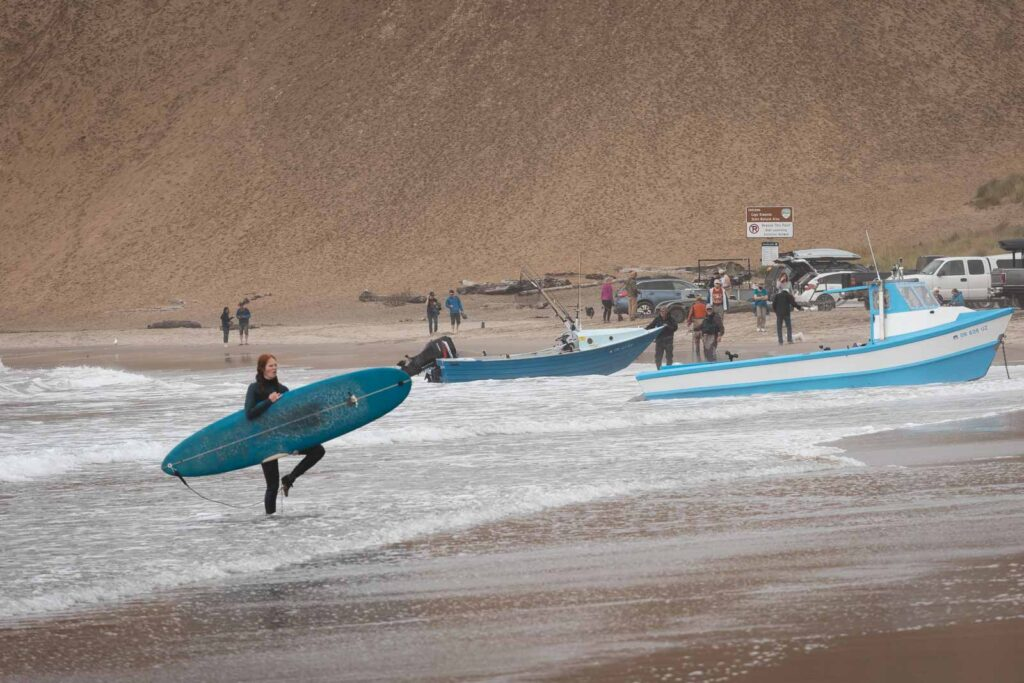 Surfer carrying surfboard and other people on Cape Kiwanda beach in Oregon