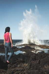 Woman standing and looking out over ocean blowhole at Devil's Churn in Oregon
