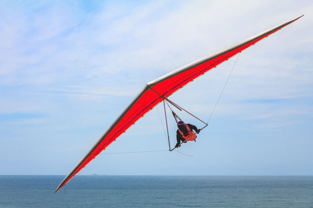 Hang gliding man flying on an orange wing near Pacific City, Oregon